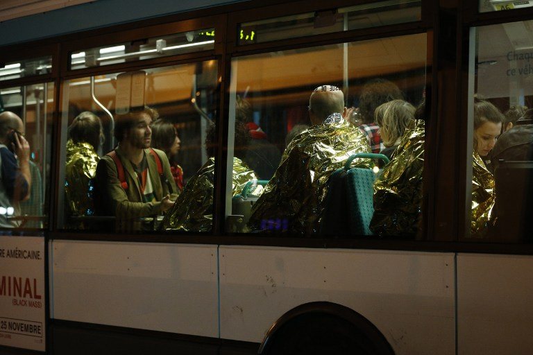 MORE EVACUATIONS. People are evacuated by bus, near the Bataclan concert hall in central Paris, on November 14, 2015. Photo by Francois Guillot/AFP