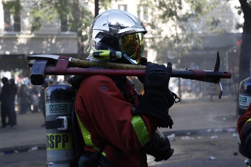 MARCH TURNS VIOLENT. A French firefighter holds an axe and a sledgehammer on his shoulder during a climate change protest in Paris on September 21, 2019. Photo by Zakaria Abdelkafi/AFP
