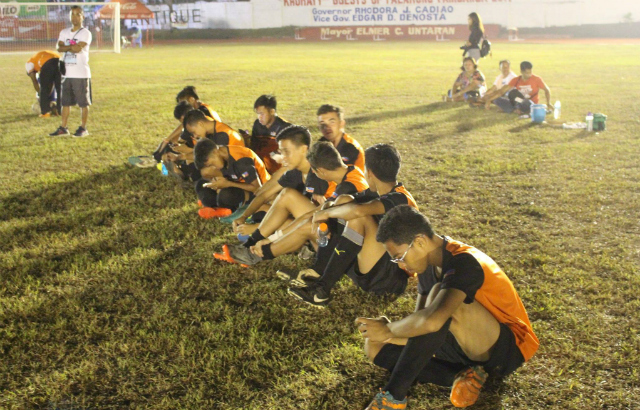 PROTEST. Region X football team sit in the Binirayan Sports Complex on Monday night, April 24 to protest NCR's no-show. Photo by JP Punzalan/Rappler
