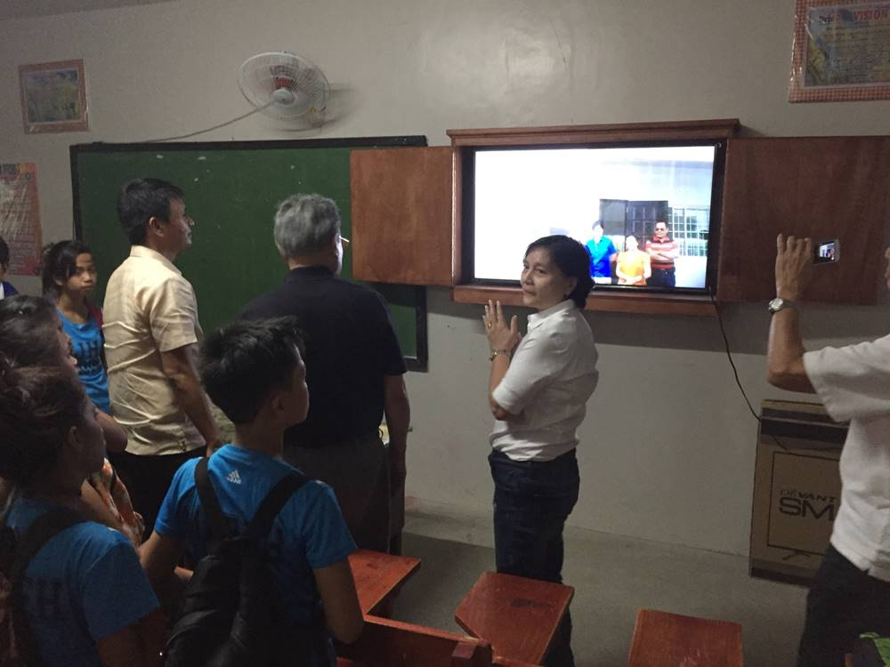 EQUIPPING SCHOOLS. Then-mayor Gloria Congco shows to public school students in Sitio Saint Joseph the learning equipment donated by partners from the private sector. Photo courtesy of Kaya Natin