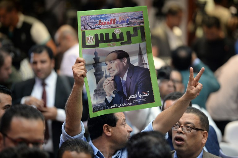 WINNER. An Egyptian man carries a copy of a newspaper, bearing the portrait of Egyptian President Abdel Fattah al-Sisi, during a press conference by the National Elections Authority in Cairo on April 2, 2018, to announce official result of Egypt presidential election. Photo by Mohamed El-Shahed