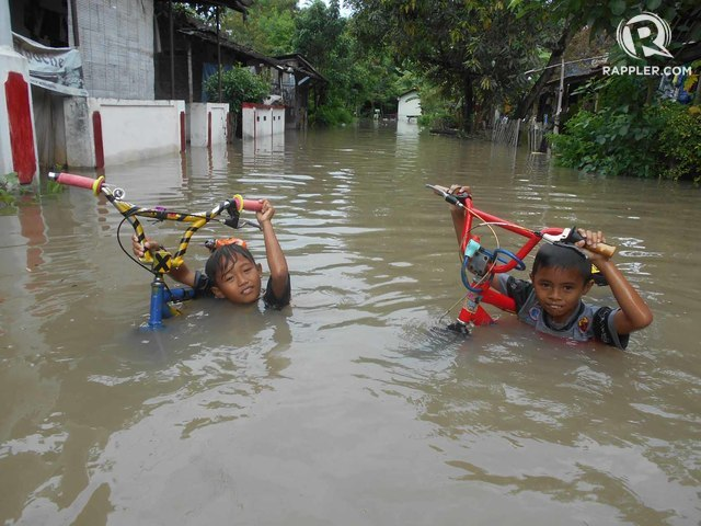Ilustrasi. Dua anak menenteng sepeda saat banjir merendam hampir semua rumah di Dukuh Kaliwingko, RT 03/RW I, Madegondo Grogol, Sukoharjo. Foto oleh Fariz Fardianto/Rappler