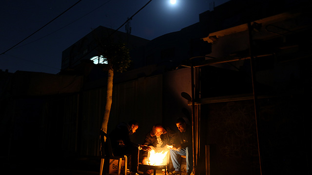 NOWHERE TO GO. Palestinian refugees sit around a fire during a power outage in Al Shateaa refugee camp next the beach in the west of Gaza City on, 27 December 2015. Mohammed Saber/EPA