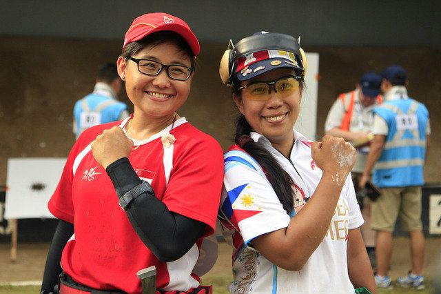 Elvie Baldivino (R) poses with Singapore's Norizan Mustafa after winning gold in the women's precision pistol event. Photo by Singapore SEA Games Organising Committee/Action Images via Reuters