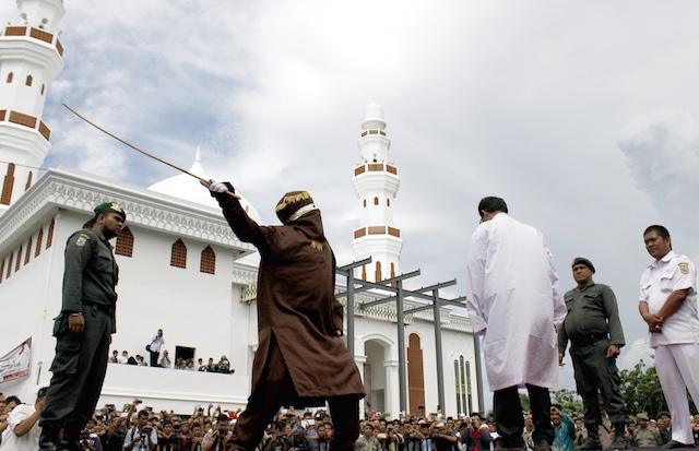 Seorang warga Aceh menerima hukuman cambuk. Pelaku dihukum menurut hukum syariat Islam, bagi mereka yang berjudi, mabuk, atau pelaku LGBT. Foto oleh EPA