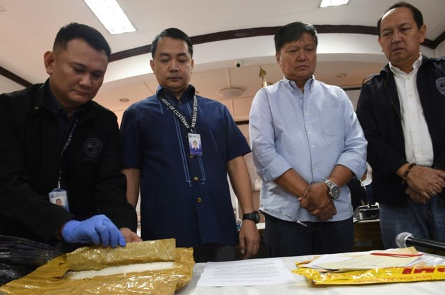BACK IN BOC. Deputy Commissioner Ariel Nepomuceno (second from left, in blue) looks through seized shabu with other customs officials. File photo by Ted Aljibe / AFP