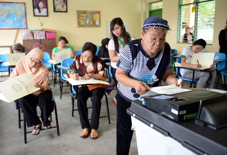 HIGH TURNOUT? An elderly voter places her ballot on a precinct count optical scan machine (PCOS) after casting her vote during mid-term elections in Manila on May 13, 2013. File photo by Ted Aljibe/AFP