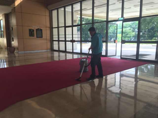 FOR THE ENTRANCE. The red carpet in front of the plenary hall is being vacuumed by a maintenance staff member. Photo by Mara Cepeda/Rappler