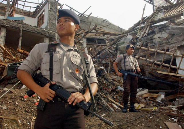 Policemen stand guard at bomb site during a purification ceremony in Kuta, Denpasar Bali, 15 November 2002, one month after a horrific bomb attack killing more than 190 people and injuring over 300 others. WEDA / AFP