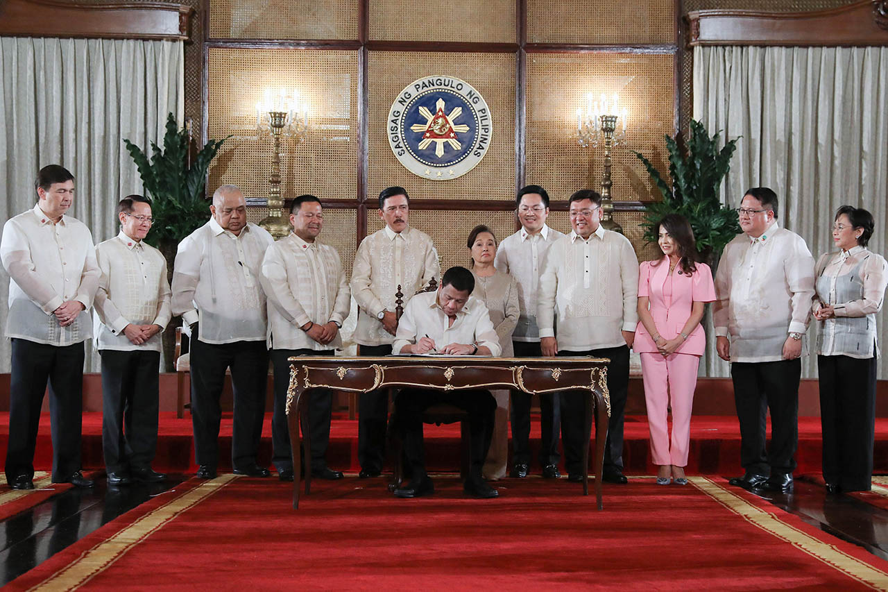 LANDMARK LAW. President Rodrigo Roa Duterte leads the ceremonial signing of the Universal Health Care Act, with congressional leaders and some lawmakers who spearheaded the bill. Malacau00f1ang photo
