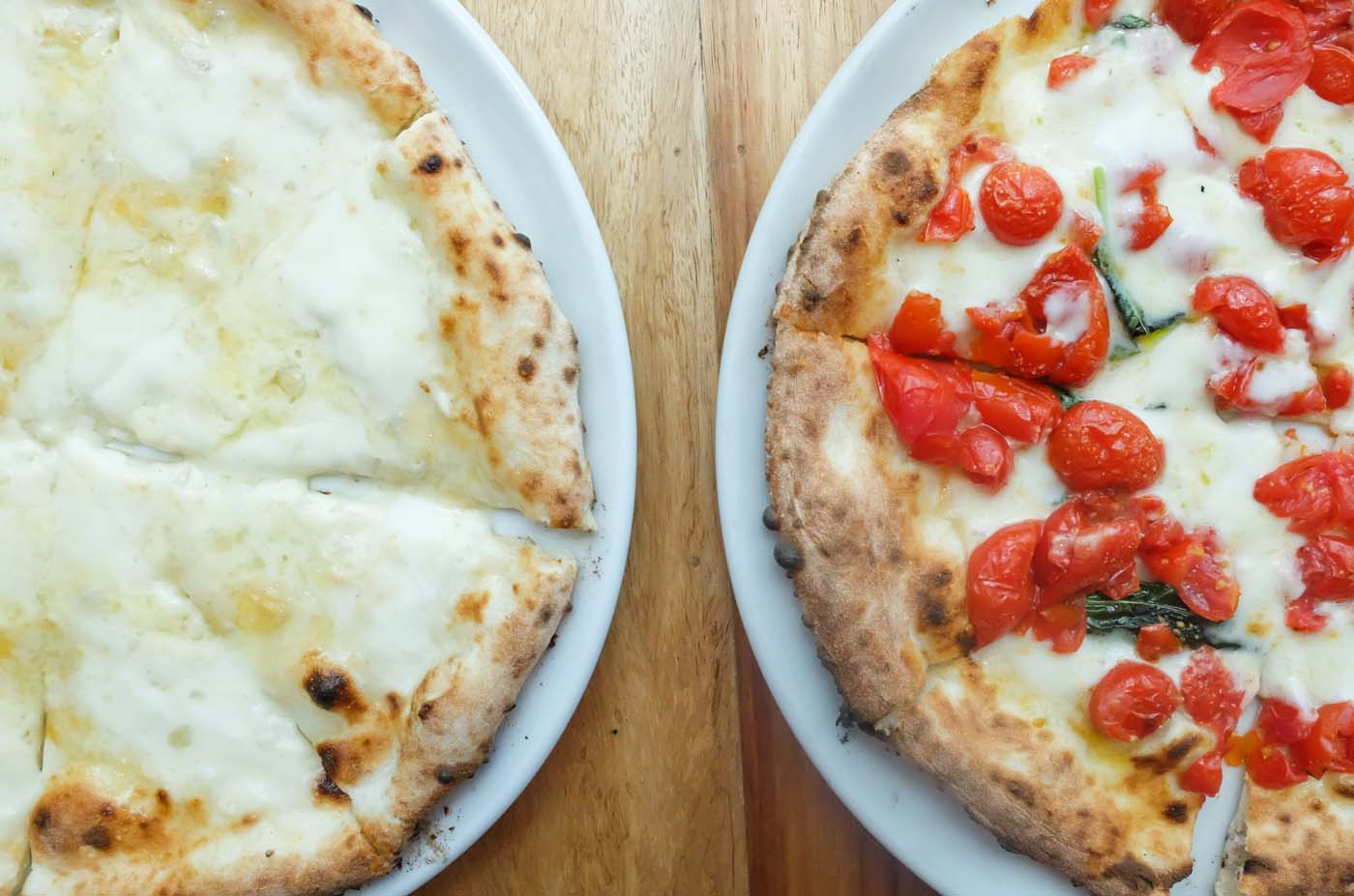 SIDE BY SIDE. The DOC vs the classic four-cheese pizza. Both are a feast for the palate, with an option to enjoy the latter with a drizzle of honey on top