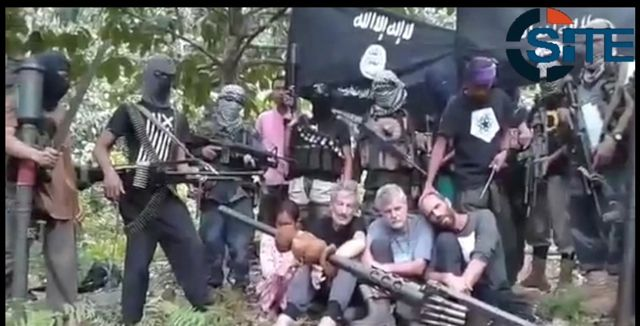 CAPTIVE. The hostages are seen surrounded by masked gunmen in a jungle setting. Video screengrab from SITE Intelligence Group