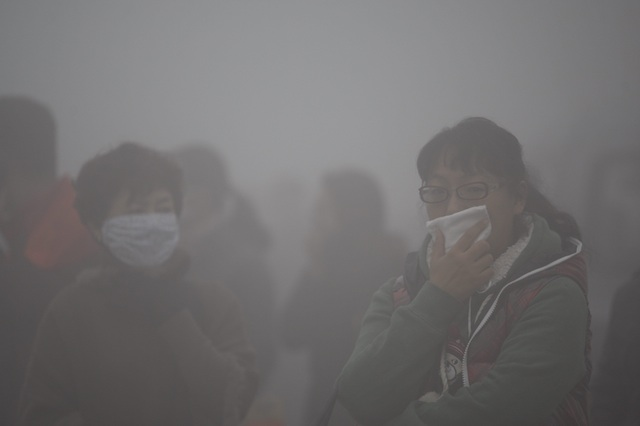 IN THE SMOG. Commuters cover their mouths while waiting for buses in the heavy fog and smog in Harbin, Heilongjiang province, China. Photo by Hao Bin/EPA