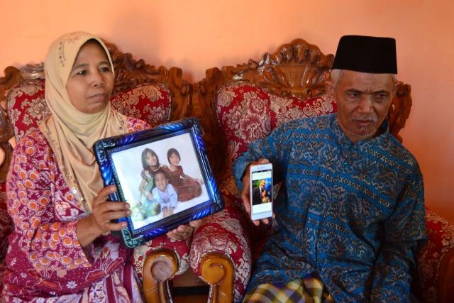ORANG TUA BANGGA. Kedua orang tua Ima, Alimah (kiri) dan Turiyo (kanan) tengah menunjukkan foto Ima bersama Presiden Barack Obama dan ketiga cucu mereka pada Senin, 25 Juli. Foto oleh Dyah Ayu Pitaloka/Rappler