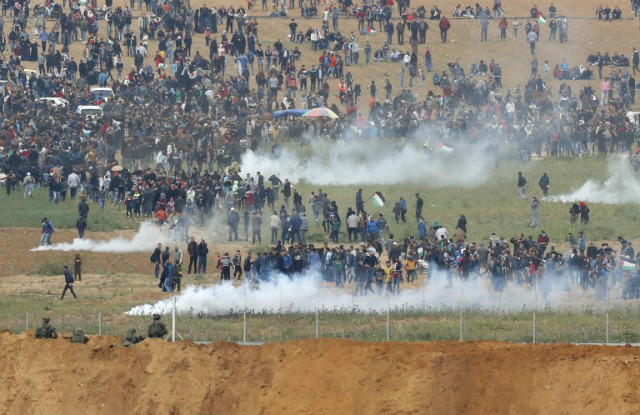 CLASHES. A picture taken on March 30, 2018 from the southern Israeli kibbutz of Nahal Oz across the border from the Gaza strip shows tear gas grenades falling during a Palestinian tent city protest commemorating Land Day, with Israeli soldiers seen below in the foreground. Photo by Jack Guez/AFP