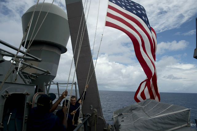 DISPUTED WATERS. US Navy personnel raise their flag during the bilateral maritime exercise between the Philippine Navy and US Navy dubbed Cooperation Afloat Readiness and Training (CARAT 2014) aboard the USS John S. McCain in the South China Sea near waters claimed by Beijing on June 28, 2014. Photo by Noel Celis/Pool/EPA