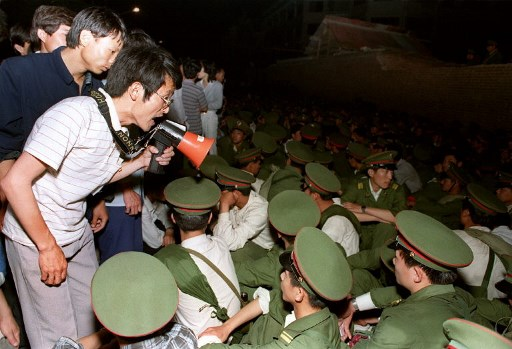 STUDENT'S VOICES. Using a loudspeaker, a student asks soldiers to go back home as crowds flooded into the central Beijing on June 3, 1989. On the night of June 3 and 4, 1989, Tiananmen Square sheltered the last pro-democracy supporters. Photo byu00c2u00a0Catherine Henriette/AFP