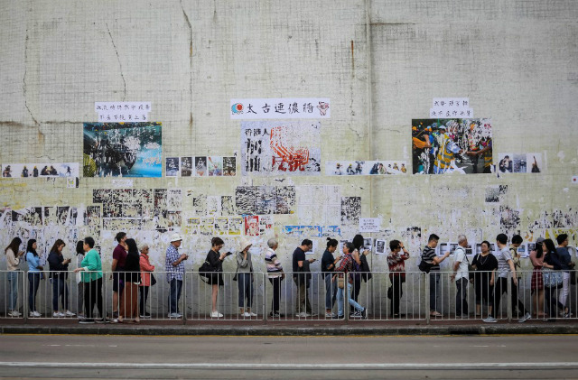 VOTE. People queue to cast their vote in front of a 'Lennon Wall' adorned with tattered posters in support of the ongoing protests, during the district council elections in Tai Koo in Hong Kong on November 24, 2019. Photo by Vivek Prakash/AFP