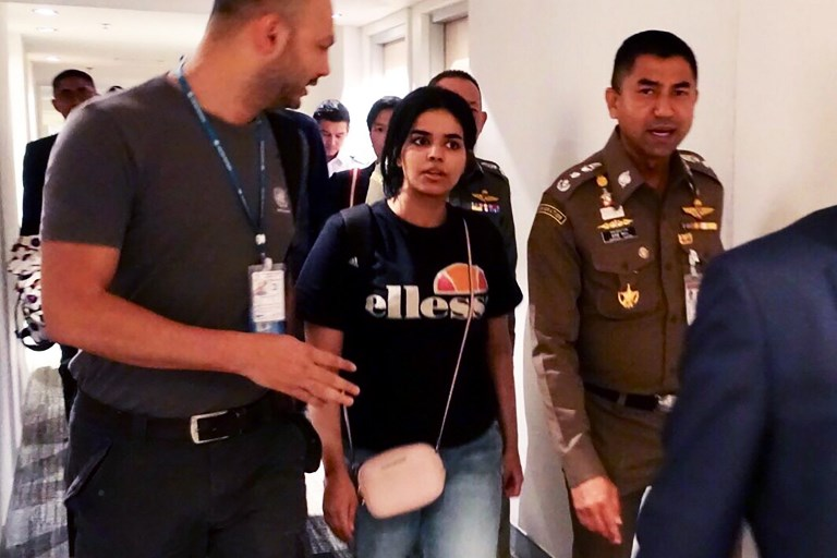 REFUGEE POLICY. This handout picture taken by the Thai Immigration Bureau on January 7, 2019 Saudi woman Rahaf Mohammed al-Qanun being escorted by a Thai immigration officer and UNHCR officials at Suvarnabhumi international airport in Bangkok. Handout / Thai Immigration Bureau / AFP