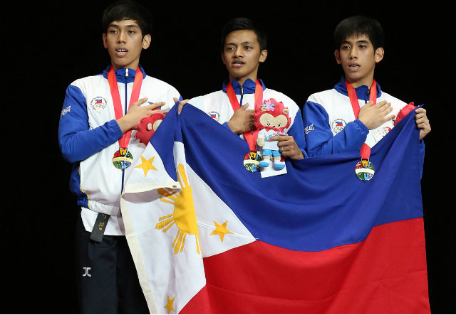 Dustin Jacob Mella, Rodolfo Reyes Jr and Raphael Enrico Mella hold their nation's flag after receiving their gold medals. Singapore SEA Games Organising Committee/Action Images via Reuters
