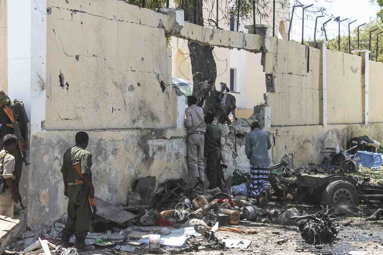 AFTERMATH. Somali security officers take a peek through a hole on the wall caused by explosion at a government builidng that was attacked by militants from Islamist group al-Shabab in Mogadishu, Somalia, 14 April 2015. Photo by Yusuf Warsame / EPA