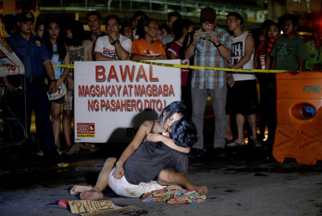 'I'M A PUSHER.' A woman hugs her husband who was shot dead by an unidentified gunman in Manila on July 23, 2016. Another photo of the same scene was published by the Philippine Daily Inquirer on July 24, 2016. Photo by Noel Celis/AFP