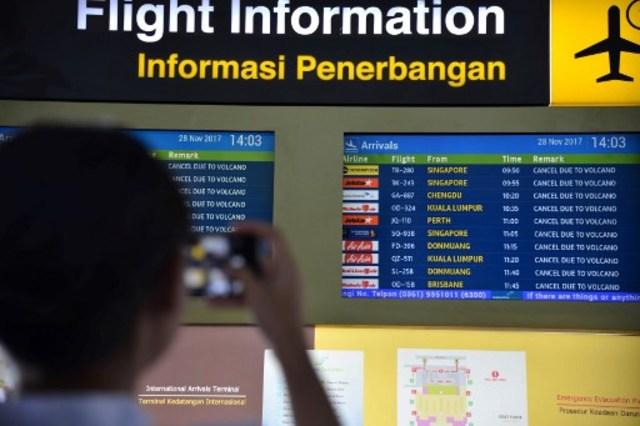 Seorang calon penumpang melihat pap an informasi di Bandara International Ngurah Rai, Bali, Selasa (28/11). FOTO oleh JUNI KRISWANTO / AFP