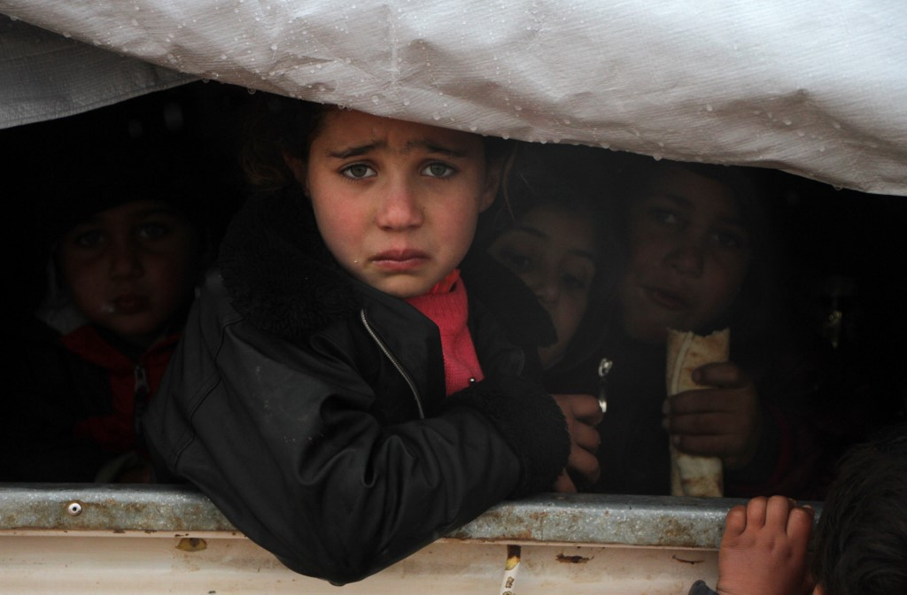UNREST. A Syrian child reacts upon her arrival in the back of a truck at a camp for displaced people near the village of Harbnoush in the Idlib province after fleeing government forces' advance on Maaret al-Numan in the south of the prvoince, on December 27, 2019.  Photo by Aref Tammawi/AFP