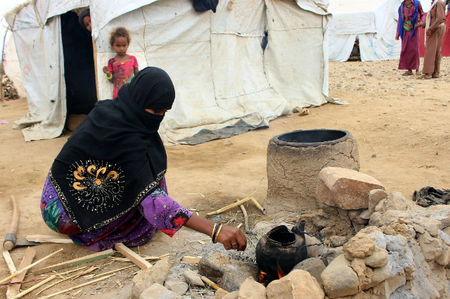 DISPLACED/ A displaced Yemeni woman from the province of Hodeidah cooks in a makeshift camp in the northern district of Abs in Yemen's northwestern Hajjah province.u00c2 File photo by Essa Ahmed/AFP
