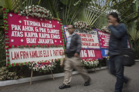 Warga melintas di antara karangan bunga berisi ucapan terima kasih kepada Basuki Tjahaja Purnama dan Djarot Saiful Hidayat di kawasan Balai Kota DKI Jakarta, Jakarta, Senin (9/10). Foto oleh Aprillio Akbar/ANTARA