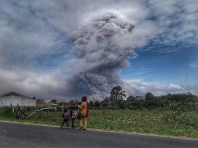 Warga melihat Gunung Sinabung menyemburkan material vulkanik saat erupsi, di Karo, Sumatera Utara, Rabu (2/8). Foto oleh Maz Yons/ANTARA