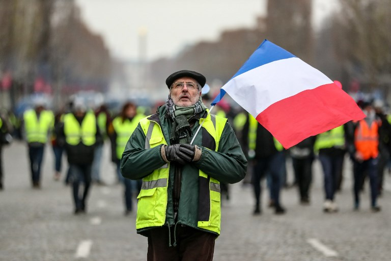 PROTESTS. A protester wearing a yellow vest (gilet jaune) waves the French national flag during a demonstration against rising costs of living blamed on high taxes on the Champs-Elysees in Paris, on December 15, 2018. File photo by Zakaria Abdelkafi/AFP