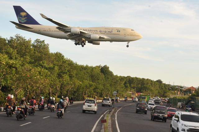 TIBA DI BALI. Pesawat Boeing 744 yang membawa Raja Arab Saudi Salman bin Abdulaziz Al Saud melintas di atas jalan sebelum mendarat di Bandara Internasional Ngurah Rai, Denpasar, Sabtu, 4 Maret. Raja Arab Saudi tersebut berwisata ke Bali selama lima hari bersama 1.500 anggota. Foto oleh Nyoman Budhiana/ANTARA