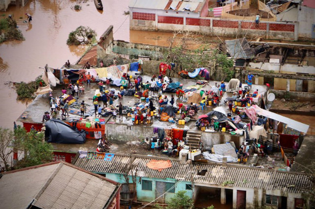 HELP. People gather on the roof of a house submerged by floods in Buzi on March 20, 2019, after tropical cyclone Idal hit Southern Africa. Photo by Adrien Barbier/AFP