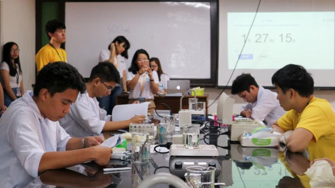 LAB SKILLS. Participants in the Laboratory Skills competition focus on their resource materials. Photo from Ateneo de Manila University
