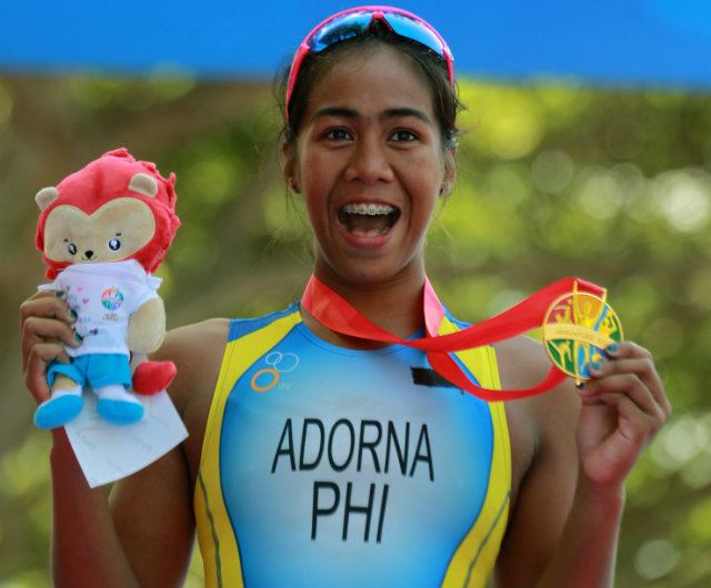 GOLDEN GIRL. An ecstastic Adorna shows of her women's triathlon gold u2013 the countryu2019s first at the 28th Southeast Asian Games. Photo by Reuters