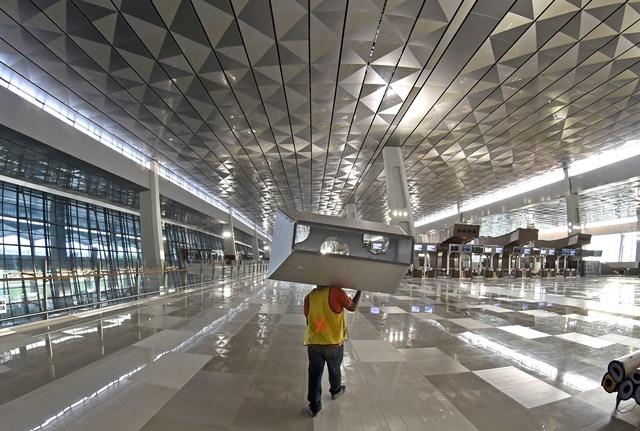 Pekerja membawa peralatan yang akan dipasang di Terminal 3 Ultimate, Bandara Internasional Soekarno Hatta, Tangerang, Banten, Senin, 1 Juni. Foto oleh Fanny Octavianus/ANTARA