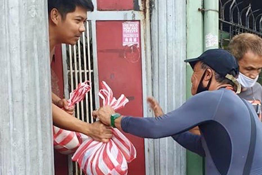 HOUSE-TO-HOUSE. Barangay captain Rodolfo Palma distributes relief goods. Photo from Palma