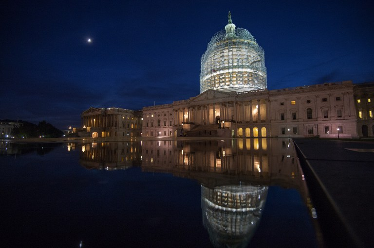 Cocooned in scaffolding, the US Capitol dome is seen in a reflecting pool on October 28, 2014 in Washington, DC. Paul J. Richards/AFP
