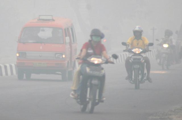 KABUT ASAP. Pengendara motor melalui daerah yang diselimuti kabut asap di Palangkaraya, Kalimantan Tengah, 18 Oktober 2006. Foto oleh Seto Ramdani/EPA