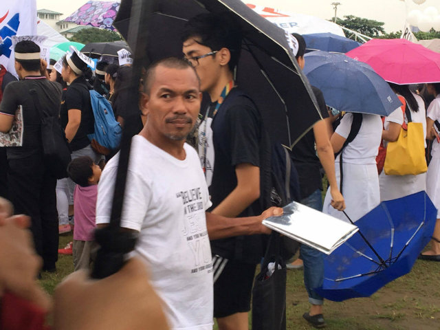 SLOW BUSINESS. Baylon sells foil covers to protesters who want to sit on the muddy grounds at the Quirino grandstand. Photo by Khristine Montenegro/Rappler