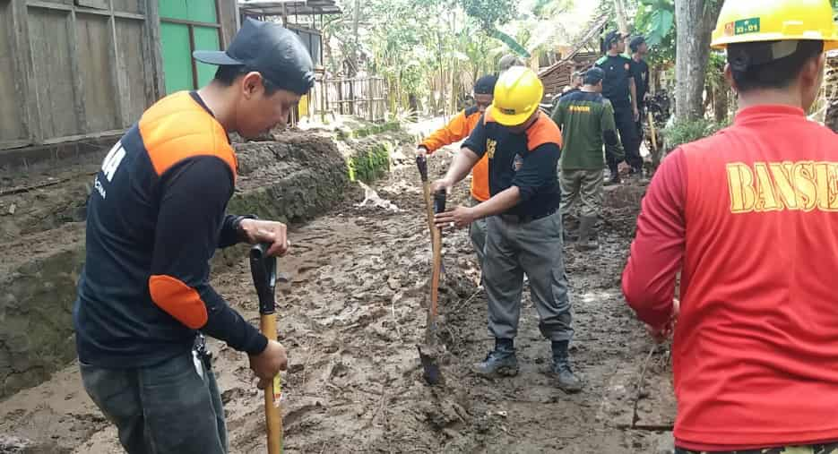Warga bersama GP Ansor membersihkan jalanan yang tertutup lumpur akibat banjir di Dusun Ngrancah Desa Sriharjo Imogiri Bantul. Foto diambil dari @TRCBPBDDIY/twitter