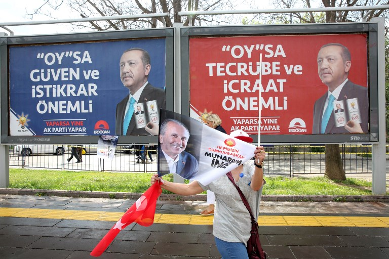 CAMPAIGN. A supporter of the presidential candidate of Turkey's main opposition Republican People's Party Muharrem Ince waves flags as she walks past election campaign posters for Turkish President Recep Tayyip Erdogan during an election rally in Ankara on June 22, 2018. Photo by Adem Altan/AFP