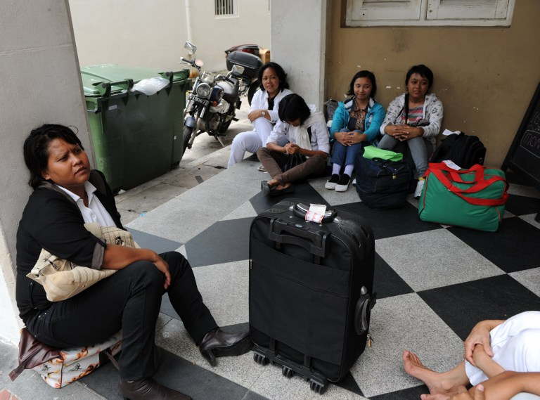 DOMESTIC WORKERS. Indonesians wait for their transportation to a maid agency after going through medical check in Singapore on in March 2012. Singapore's decision to grant a mandatory weekly day off for foreign maids was welcomed by social workers and human rights groups, but some employers were unhappy. File photo by Roslan Rahman/AFP