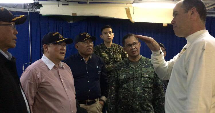 CAPS. Philippine officials wear USS Carl Vinson caps given as presents by the US Navy. Photo by Camille Elemia/Rappler
