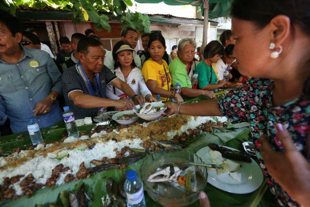 CAMPAIGN STYLE. Vice President Jejomar Binay joins Quezon residents in his favorite boodle fight. OVP photo