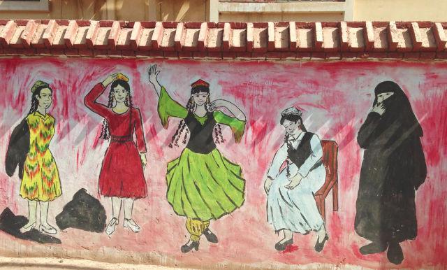 PROPAGANDA MURAL. A propaganda mural in Turpan, Xinjiang, 2017, encouraging women to cast off their Islamic dress and embrace their so-called indigenous culture. u00c2u00a9 Coda Story