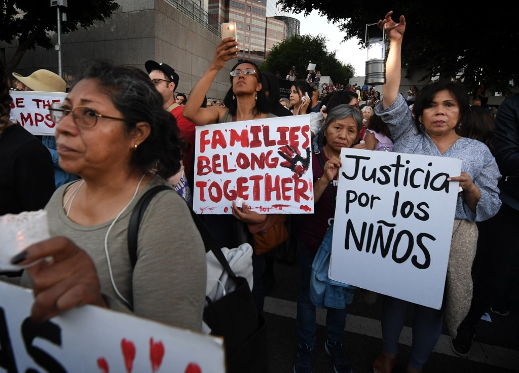 JUSTICE FOR KIDS. People protest against the upcoming ICE raids and detentions of refugee asylum seekers at a vigil outside the main ICE detention center (background) in downtown Los Angeles on July 12, 2019. Photo by Mark Ralston/AFP