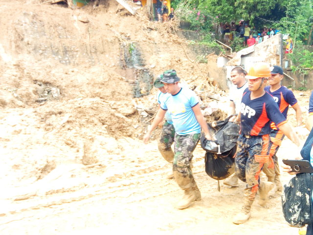 LANDSLIDE DEATHS. Search and rescue teams find bodies of some missing persons in a landslide. Photo by Mavic Conde