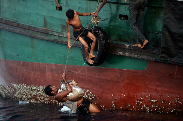 STARVING, DEHYDRATED. Rohingya migrants bring back food supplies dropped by a Thai army helicopter after jumping to collect them at sea from a boat drifting in Thai waters in the Andaman sea on May 14, 2015. Photo by Christophe Archambault/AFP